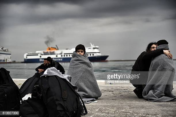 TOPSHOT Children wrapped in covers stand in a harbour as migrants and refugees arrive on the Greek island of Lesbos while crossing the Aegean Sea...