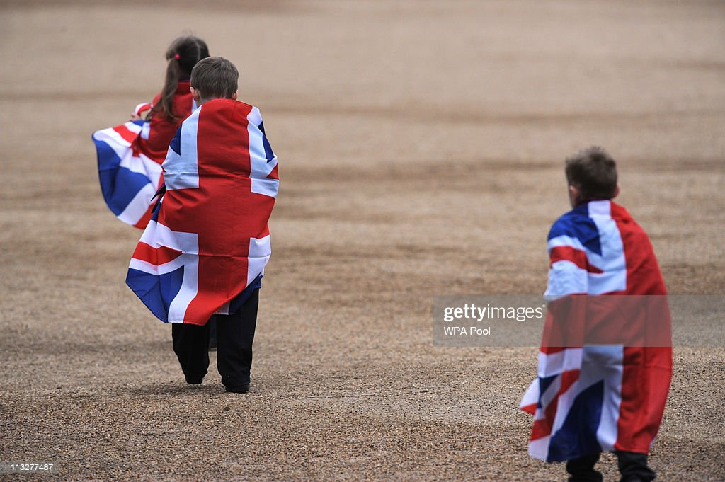 Children wrapped in union jack flags walk along The Mall to Buckingham Palace following the wedding of Prince William to Kate Middleton on April 29, 2011 in London,England.