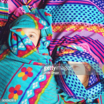 Children wrapped up in colourful blankets