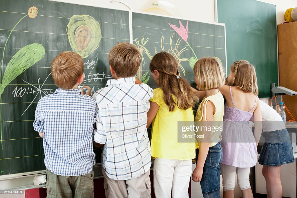 Children writing and drawing on blackboard : Foto de stock