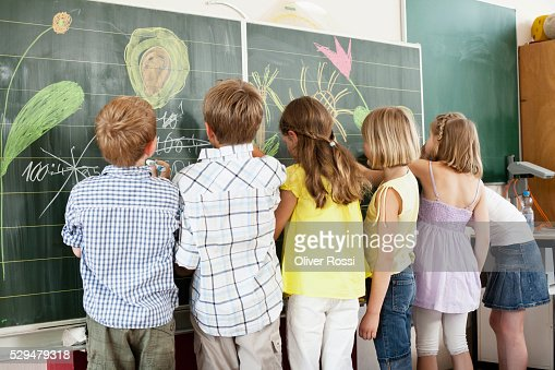 Children writing and drawing on blackboard : Stockfoto