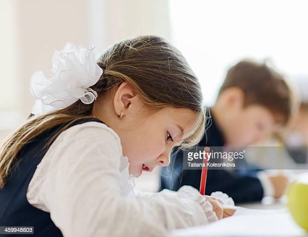 Children writing drawing in class