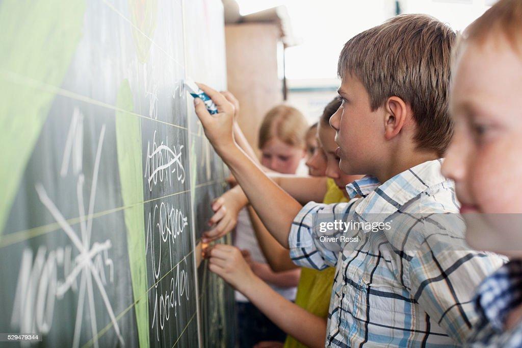 Children writing on blackboard : Stockfoto