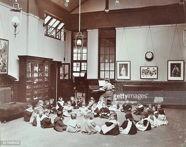 Children's band Southfields Infants' School Wandsworth London 1906 A class of infant schoolchildren sit in a circle on the floor while their teacher...