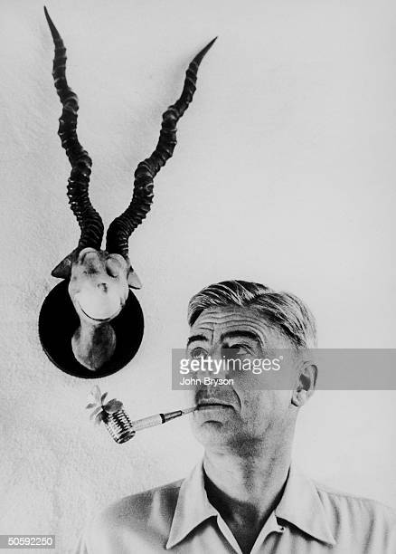 Children's book author Theodor Seuss Geisel with a whimsical plantsprouting corncob pipe in his mouth standing under his 1940 sculpture of a...
