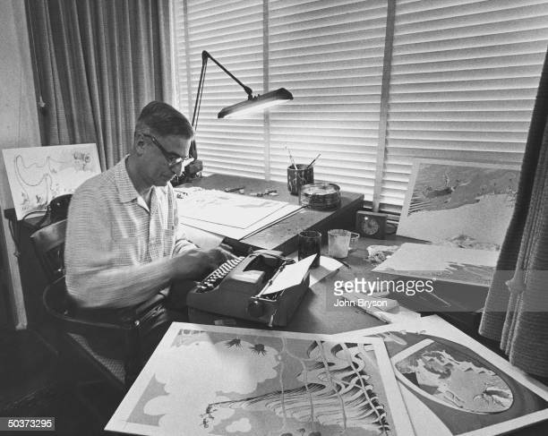 Children's book author Theodor Seuss Geisel working at his typewriter in his studio on a new book and surrounded by some of his illustrations for the...