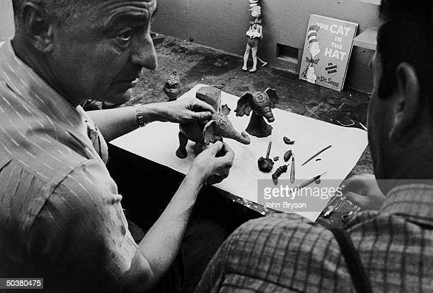 Children's book author/illustrator Theodor Seuss Geisel working on clay models of some of the characters he has created