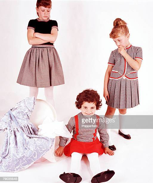 Group of three young girls model a variety of outfits made of dog tooth check and gingham fabrics with contrasting details The youngest girls sits on...