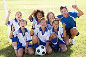 Group Of Children In Soccer Team Celebrating With Trophy By Goal On Playing Field
