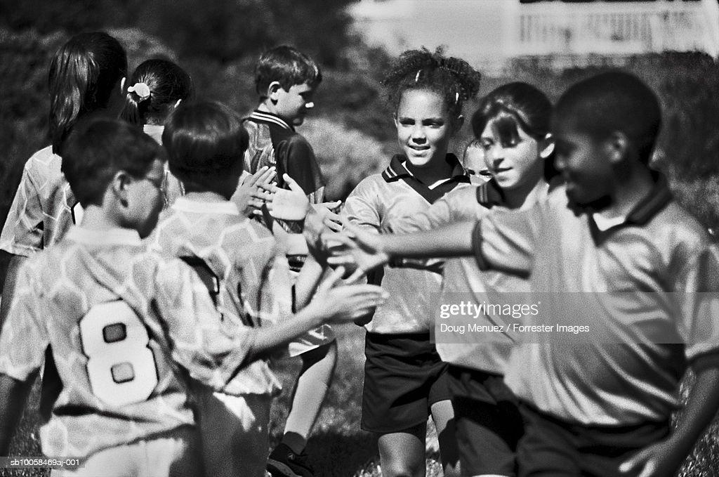Childrens football teams shaking hands (B&W) : Stock Photo