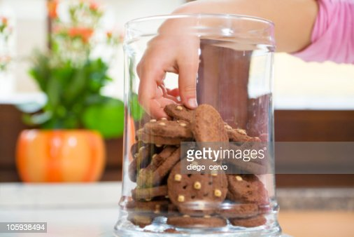 Children's hand in the cookie jar grabbing a cookie : Stock Photo