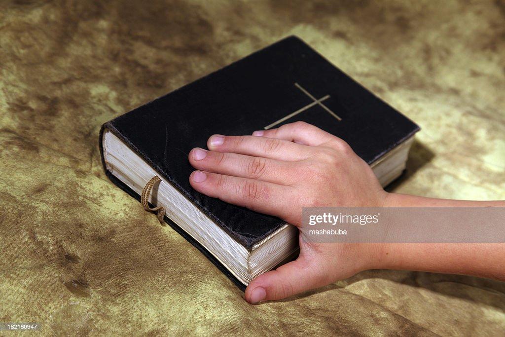 Children's hand on bible.