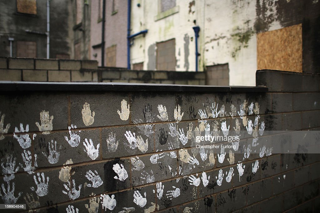 Children's hand prints adorn the garden wall of empty former council houses in a street in the Lancashire town of Accrington as they wait to be modernised by private developers on January 3, 2013 in Accrington, England. There are estimated to be 850,000 empty homes in the United Kingdom even though local councils still have long waiting lists for housing. The terraced houses were due to be rejuvenated by Accrington council but the project was put on hold when the government cut a housing regeneration project.
