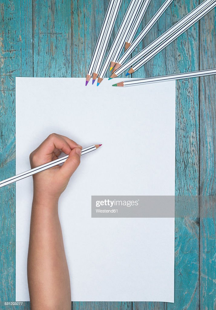 Childrens hand with colored pencils and blank sheet of paper