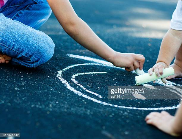 Children's Hands Drawing Picture With Sidewalk Chalk