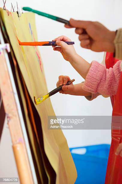 Children's hands holding paint brushes, painting picture on easel