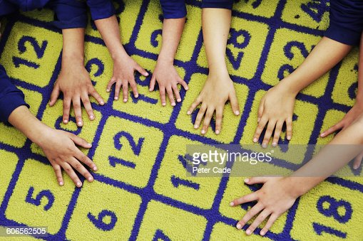 Children's hands on number carpet
