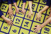 Children's hands on number carpet
