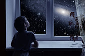 A little boy is standing near the window and looking outside, imagining boundless space with myriad of stars