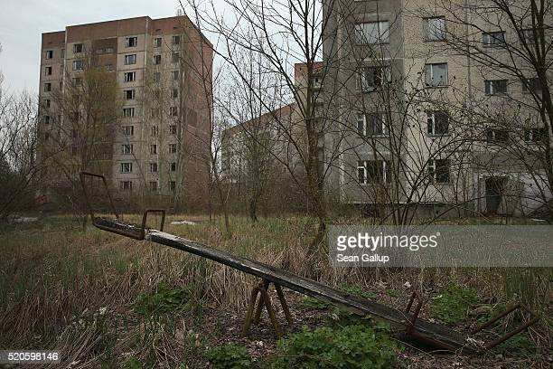 A children's seesaw stands among former apartment buildings on April 9 2016 in Pripyat Ukraine Pripyat built in the 1970s as a model Soviet city to...