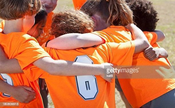 Children's sports team in huddle