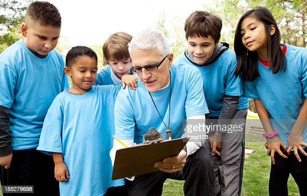 Children's sports team with coach. Practice, field, park. Preparation.