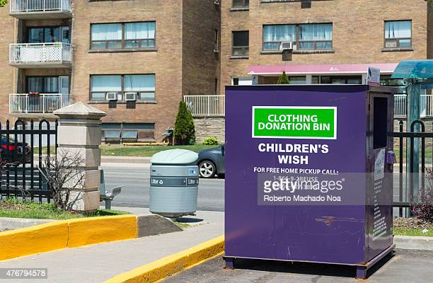 Children's Wish clothing donation bin in the street of the city over building in the background