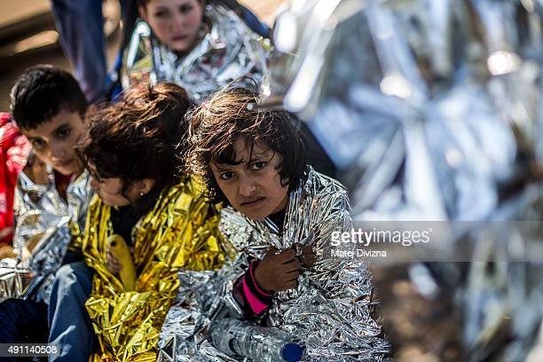 Childs are wrapped with thermal blankets to shelter from cold as they arrived with other refugees on the shores of the Greek island of Lesbos after...