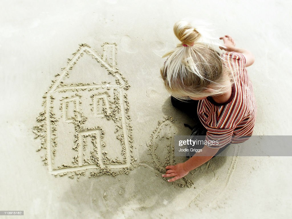 Childs drawing of house in the sand : Stock Photo