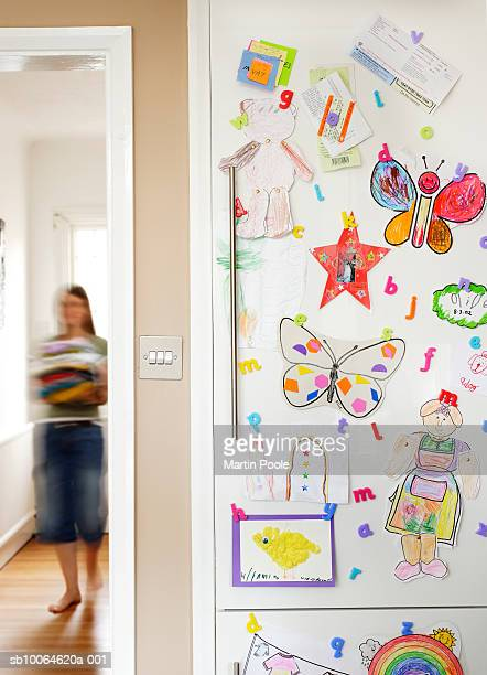 Child's drawings and magnets on fridge door, woman in background