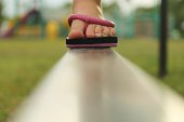 Child wearing flip flops walking on a balance beam.
