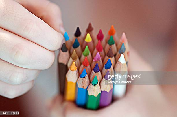 Child's hand holding coloured pencils