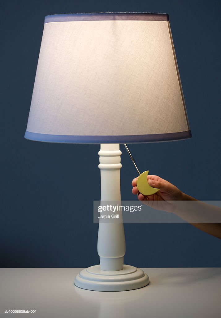 Child's hand holding switch of lamp : Stock Photo