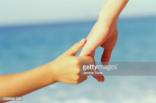 Child's hand holding woman's hand, sea in bckground, close-up : Stock Photo