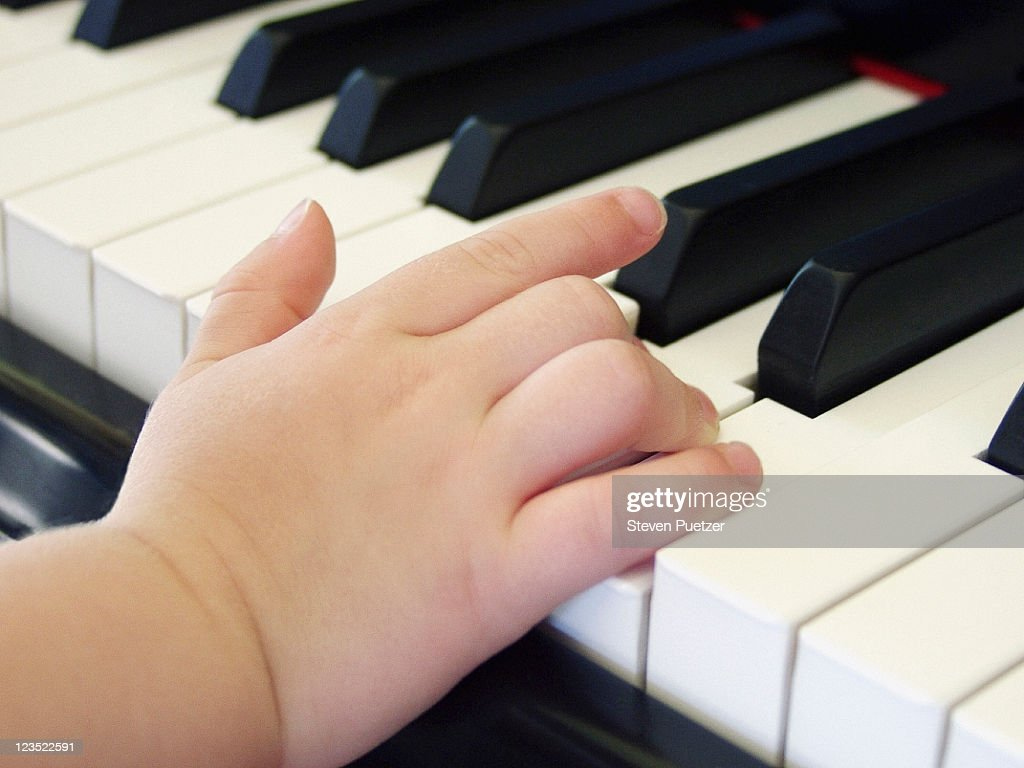 Childs hand playing piano : Stock Photo