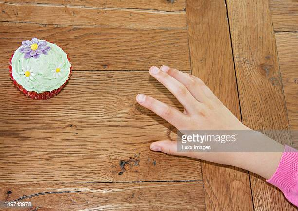 Child's hand reaching secretly for cup cake
