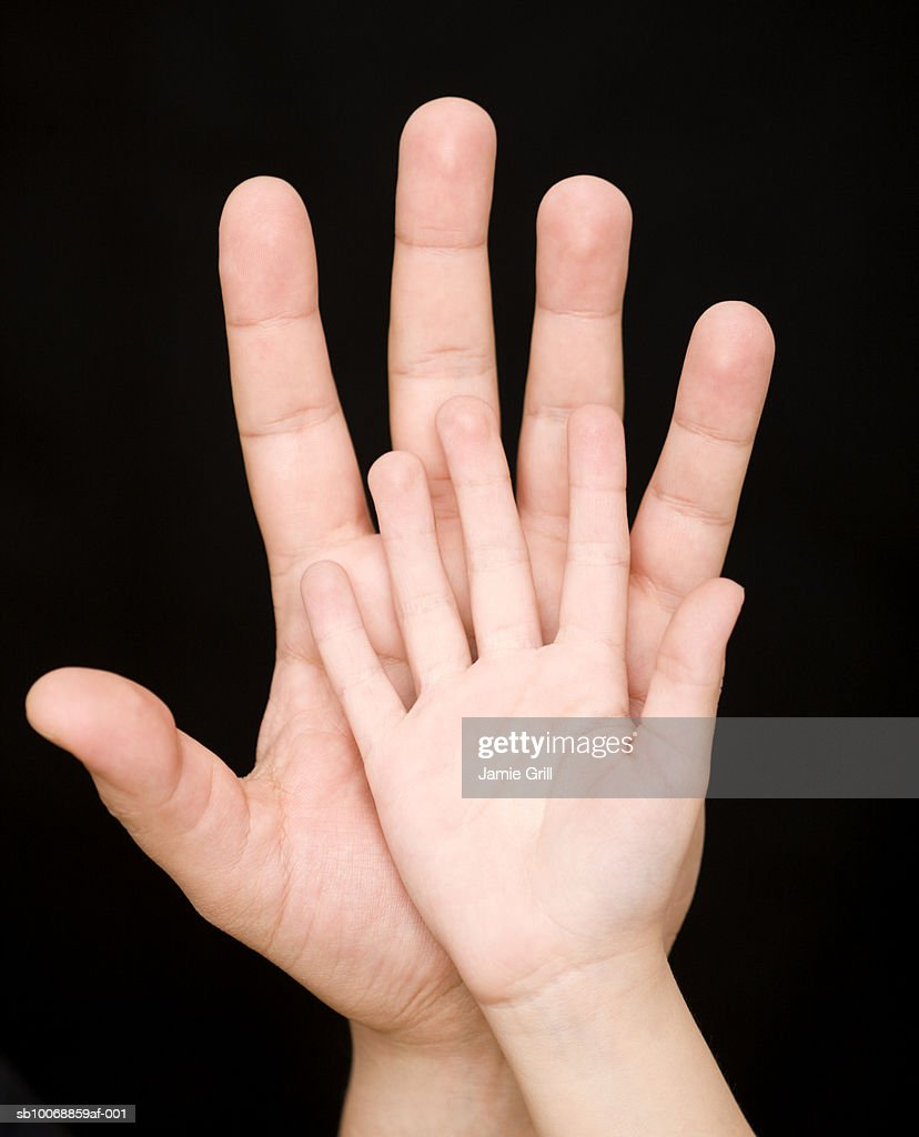 Child's hand resting on adults hand, close-up : Stock Photo