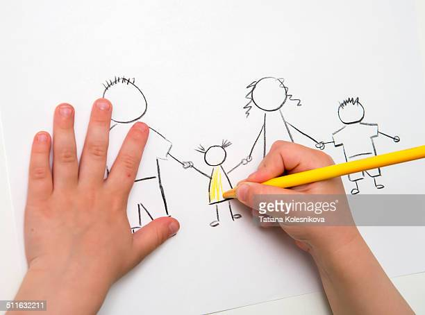Child's hands drawing a picture of a family