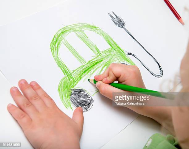Child's hands drawing an electric car