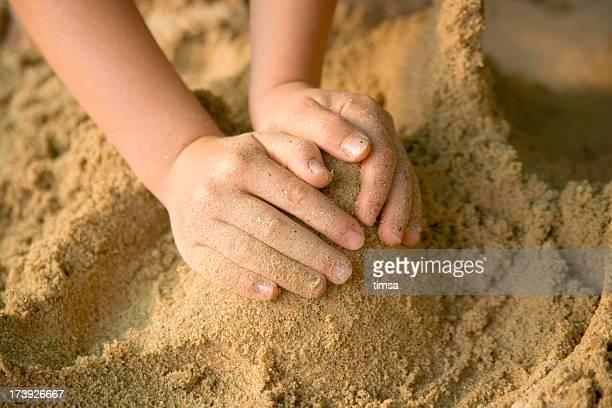 Kind s Hände bilden ein Hütchen in sand