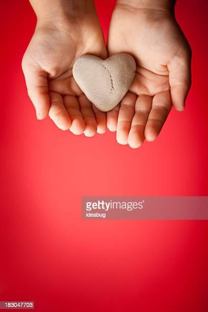 Kinder Hände halten einen herzförmigen Stein auf rotem Hintergrund