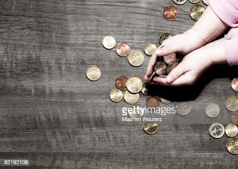 Child's hands holding coins : Stock Photo