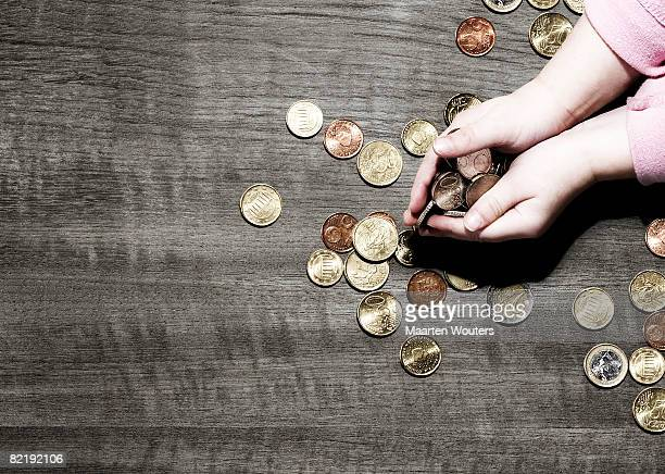 Child's hands holding coins