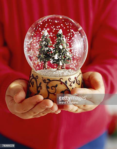 Child's hands holding snow globe