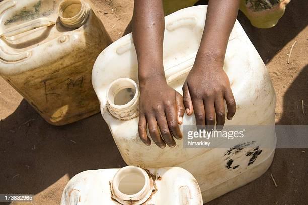 Child's hands over water jug