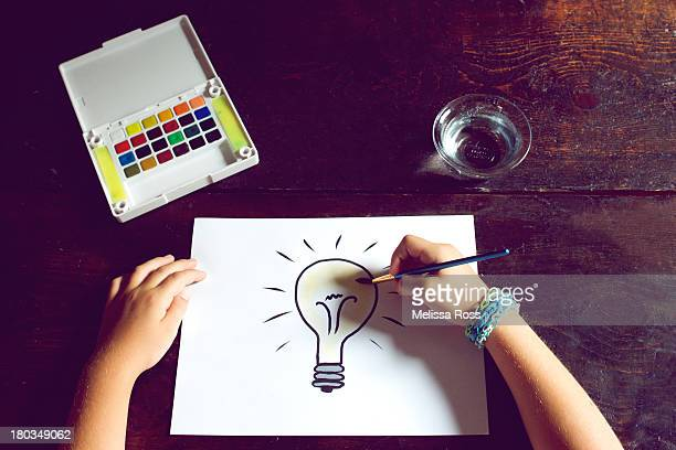 Child's hands painting a picture of a light bulb