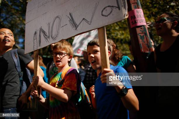 Childs hold a placard as they take part during a march in protest of President Trump's decision on DACA in front of a Trump Hotel on September 9 2017...
