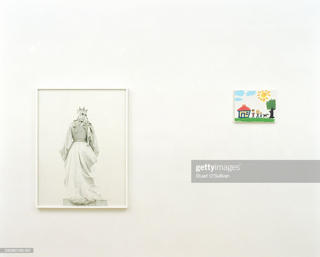 Child's painting mounted on wall next to picture in art gallery : Stock Photo