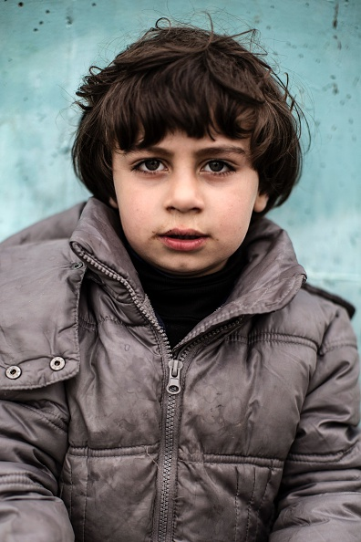 A childs poses outside a passenger terminal used as shelter for refugees and migrants in the Piraeus harbour near Athens on March 12, 2016