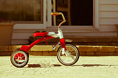Child's rusted favorite cherished red tricycle standing ready and waiting for its owner to arrive on paving outside a house